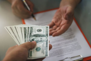 A man signing a contract and receiving a money